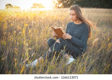 Beautiful girl sitting in the field and reading a book.