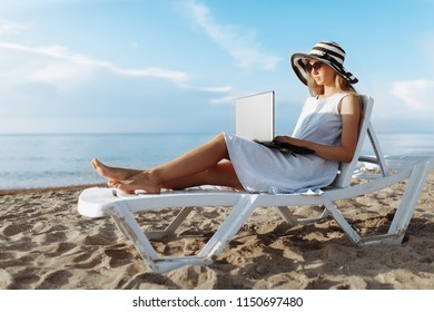 Beautiful girl sitting with a laptop on a chaise longue, a woman working on vacation