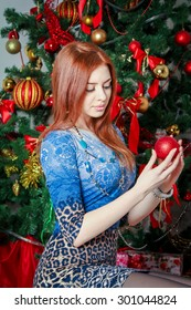Beautiful girl sitting near Christmas  tree, holding and looking at red sparkling ornament