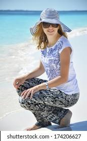 Beautiful girl sitting near the sea in summer