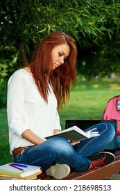 beautiful girl sitting on a bench in the park with a notebook