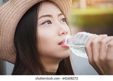 Beautiful girl sitting on the bench drinking water