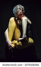 Beautiful girl sitting on black background in yellow pantyhose