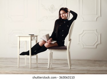 Beautiful girl sitting on a chair in a bright room with a notebook in hands