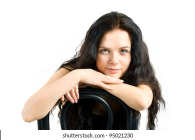 beautiful girl sitting on a chair and looks into the camera