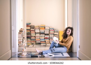 beautiful girl sitting on elegant vintage floor chooses a book from the bookshelf