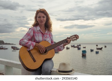 beautiful girl sitting on a fence with a guitar on the beach