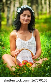 Beautiful girl sitting on grass floor and holding basket of apples