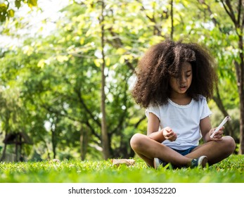 Beautiful girl sitting on green grass in a park