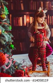The beautiful girl sitting on the hobbyhorse near Christmas Tree