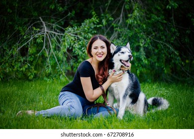 A beautiful girl is sitting on the lawn with her dog. Siberian husky dog with blue eyes. Bright green trees and grass are in the background. Friendship between man and animals.