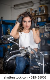 beautiful girl sitting on a motorcycle in the garage. slight blur