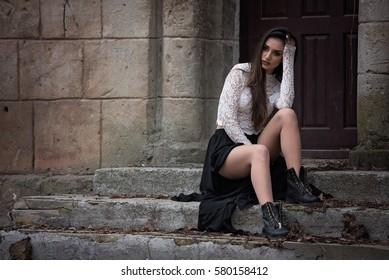 8b8d45e17 Beautiful girl sitting on old stairs at the castle. Romantic women with  long black dress