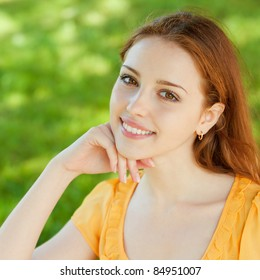 A beautiful girl is sitting on a park bench on a background of green nature
