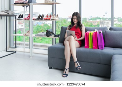Beautiful girl sitting on sofa used a tablet shopping online with colorful shopping bags