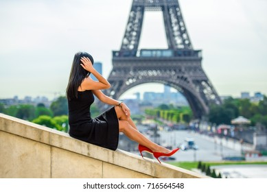 Beautiful girl sitting on the top of the wall and looking at the Eiffel tower at Trocadero square in Paris