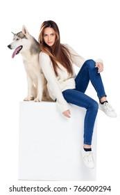 beautiful girl sitting on white cube with husky dog, isolated on white