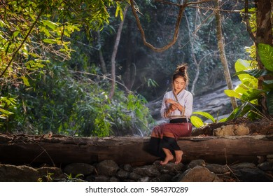 Beautiful girl sitting on wooden in a forest