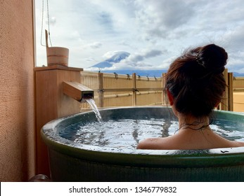 Beautiful girl sitting in onsen (mineral hot bath) and seeing Fuji mountain
