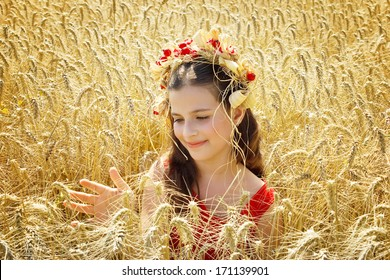 beautiful girl sitting in the wheat,best focus on a child's face, hair and wheat in front of and next to the child,