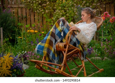 Beautiful girl sitting in a wicker rocking chair with a book, covered with a blanket. Next to the chair is a pot with a huge bouquet of wildflowers.