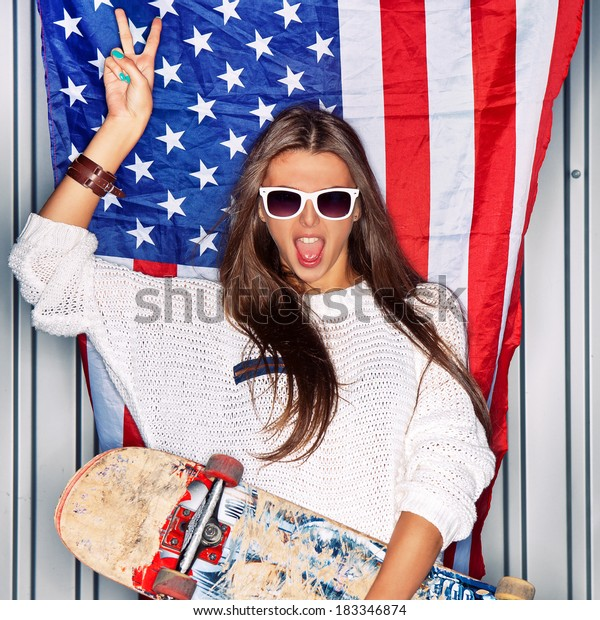 Beautiful girl with a skateboard in front of a flag of the U. S.