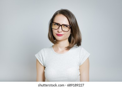 Beautiful girl skeptical wearing glasses, isolated on gray background