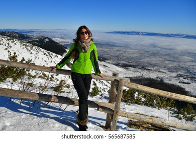 Beautiful girl in a ski suit on a background of winter mountains