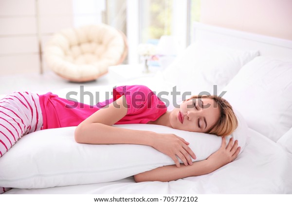 Beautiful girl sleeping with body pillow in bedroom