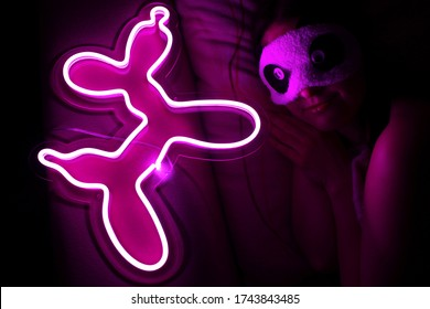 A beautiful girl is sleeping in a sleep blindfold with a purple neon sign dog. Good night. Trendy stylish. Glowing life. Modern style. Neon sign.