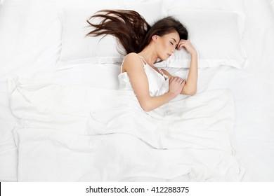 Beautiful girl sleeps in the bedroom, lying on bed .