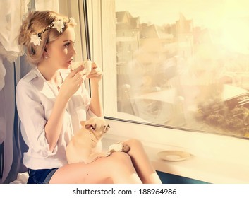 beautiful girl with small dog on knees with a cup of coffee looking through window