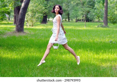 Beautiful girl with small white basket jumping high in the air on summer meadow.