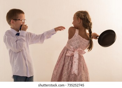 A beautiful girl in a smart pink dress and a boy wearing glasses and a tie are playing together. The concept of friendship.
