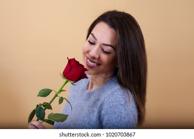 A beautiful girl smells like a red rose