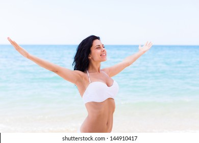 beautiful girl smile with raised hands, woman on beach summer vacation. concept of freedom travel