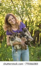 Beautiful girl smiles and holds on the arm five cute fluffy puppies of breed Siberian Laika
