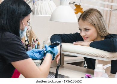 Beautiful girl smiles at the manicure master in a cozy nail salon