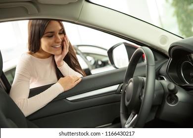 Beautiful girl smiling and admire view of automobile cabin. Female customer choosing vehicle in modern car dealership. Girl looking at steering wheel through car window.