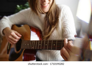 beautiful girl smiling and playing on the guitar on the floor at home. covid - 19