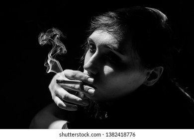 Beautiful girl smokes because of depression and stress. Black and white photo