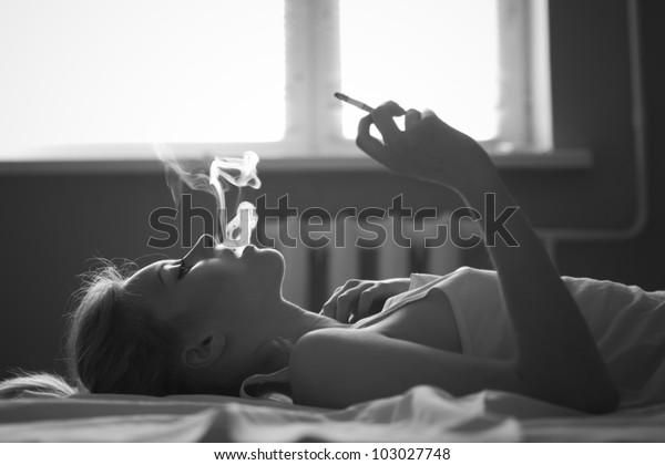 beautiful girl smokes in bed