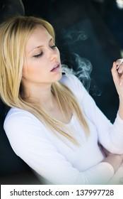 beautiful girl smokes in the car
