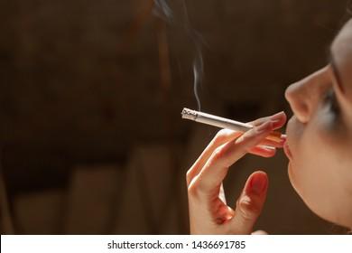 Beautiful girl smokes a cigarette in a dark building.
