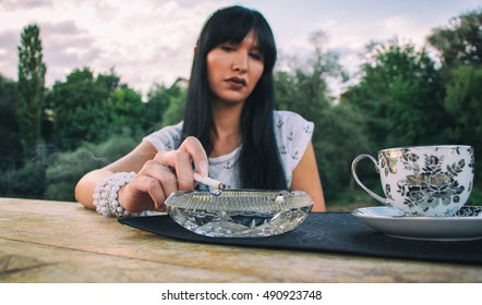 beautiful girl smokes a cigarette and drinks coffee
