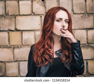 Beautiful girl smokes while waiting in the street.