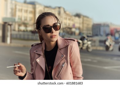 Beautiful girl smoking a cigarette and looking at the setting sun through sunglasses against a city background