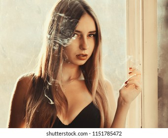 Beautiful girl smoking cigarette at window