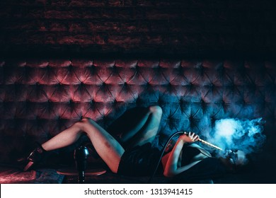 Beautiful Girl smoking hookah in Nightclub. Exhaling smoke. Sexy girl smokes hookah