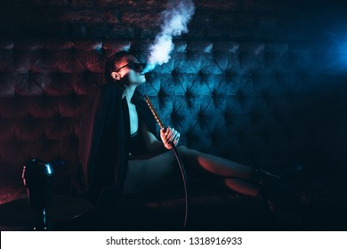 Beautiful Girl smoking hookah in Nightclub. Exhaling smoke. Sexy girl smokes hookah